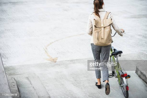 young businesswoman with backpack, pushing bicycle, rear view - radfahren stock-fotos und bilder