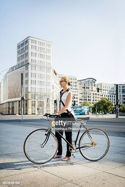 Young Businesswoman with bicycle in city