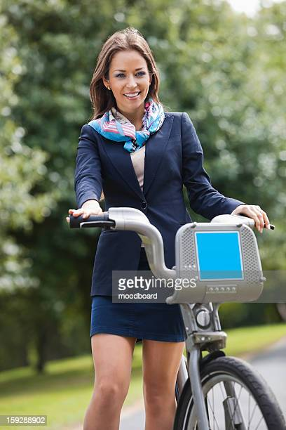 young businesswoman with bicycle standing at park - 膝から上の構図 ストックフォトと画像