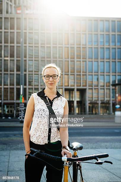 Young Businesswoman with bicycle standing in city
