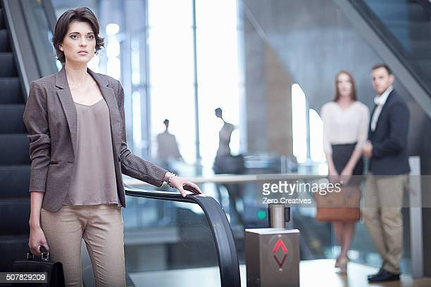 young businesswoman with briefcase on escalator in conference centre - down blouse stockfoto's en -beelden