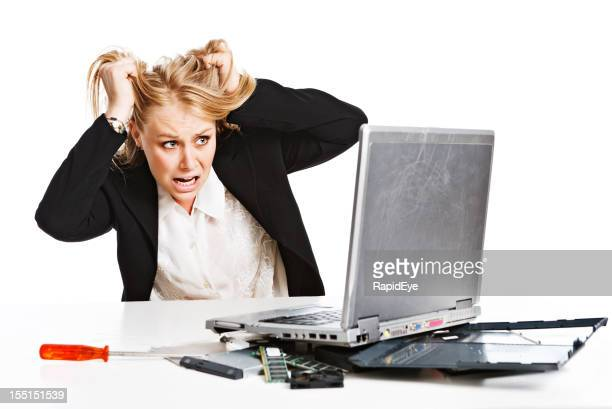 Young businesswoman with broken laptop is frustrated
