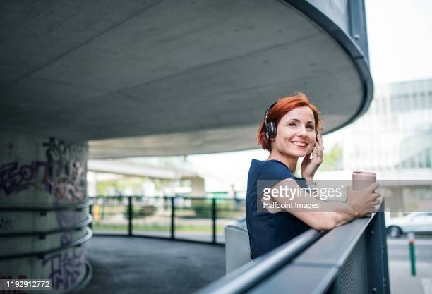 young businesswoman with coffee and headphones standing outdoors in city, listening to music. - dyed red hair stock pictures, royalty-free photos & images