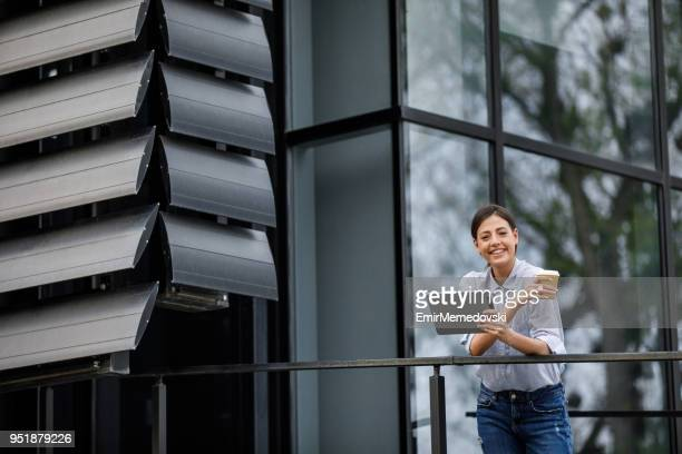 Young businesswoman with coffee cup and digital tablet outdoors