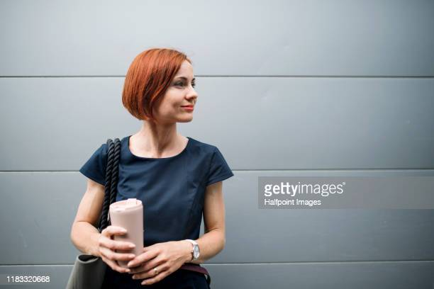 young businesswoman with coffee standing outdoors in city against gray background. - grey dress stock pictures, royalty-free photos & images