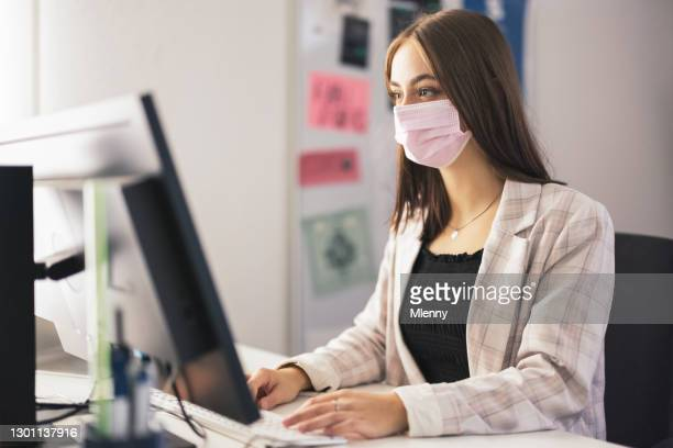 young businesswoman with coronavirus protective face mask working in office - mlenny stock pictures, royalty-free photos & images