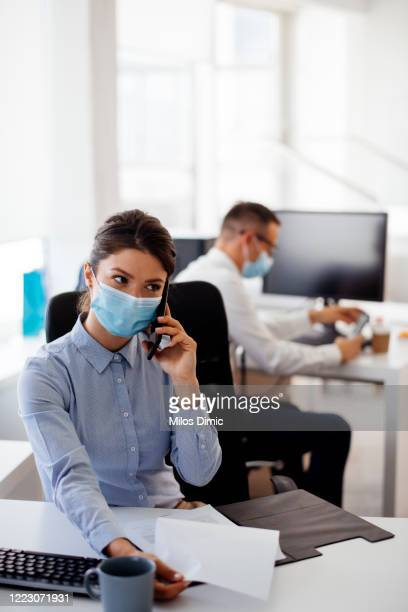 young businesswoman with face mask talking on the phone while working in the office. stock photo - social distancing stock pictures, royalty-free photos & images