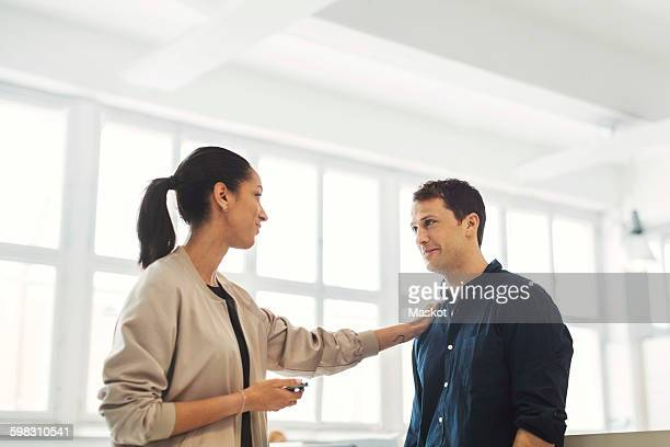young businesswoman with hand on male colleagues shoulder in office - persuasão - fotografias e filmes do acervo