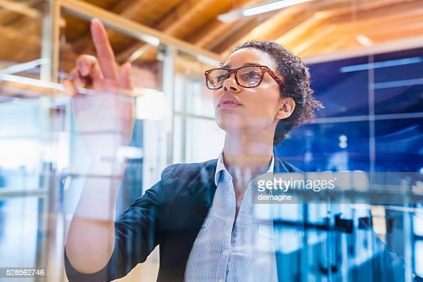 Mujer de negocios joven con dedo índice en la ventana de montaje en panel