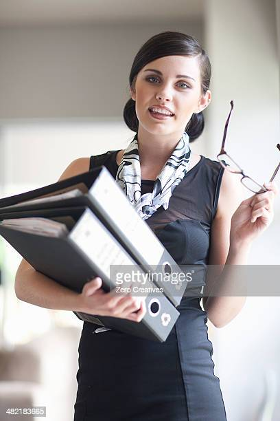Young businesswoman with paperwork files and spectacles