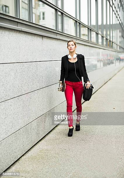 Young businesswoman with skateboard and headphones wearing red trousers