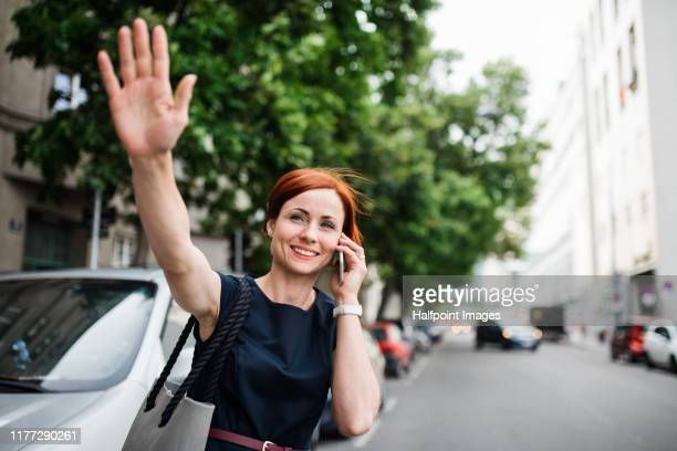 young businesswoman with smartphone standing outdoors in city, hailing a taxi. - waving stock pictures, royalty-free photos & images