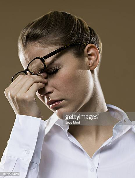 young businesswoman with spectacles rubbing nose