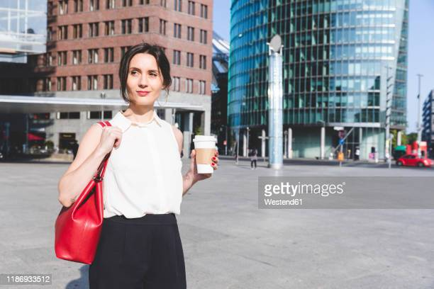 young businesswoman with takeaway coffee in the city on the go, berlin, germany - shoulder bag stock pictures, royalty-free photos & images