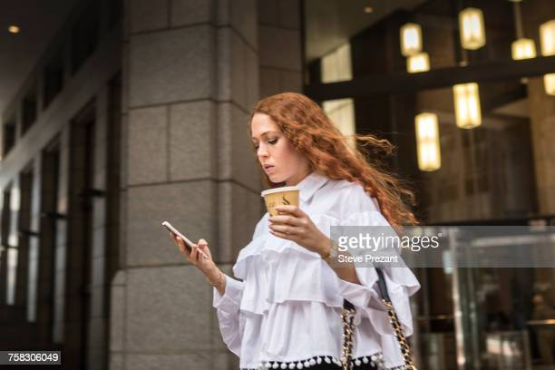 young businesswoman with takeaway coffee looking at smartphone on sidewalk, new york, usa - istantanea foto e immagini stock