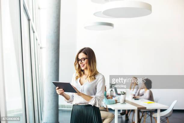 young businesswoman working in modern office on a digital tablet - business imagens e fotografias de stock