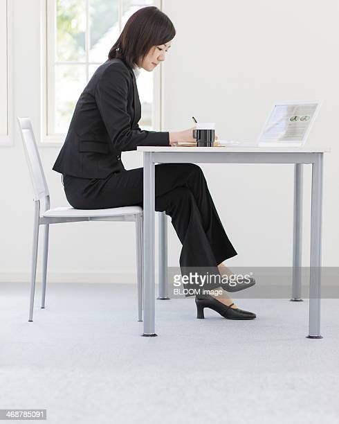 young businesswoman working in office - cross legged stock pictures, royalty-free photos & images
