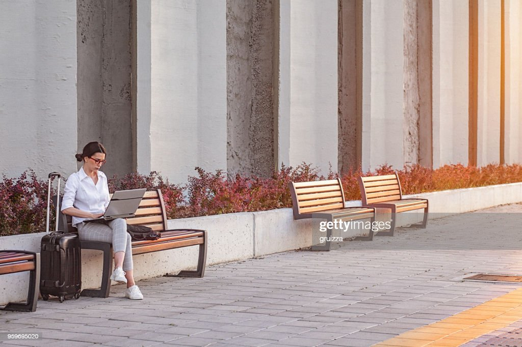Young businesswoman working on a a laptop while sitting on a bench on the city street : Stock Photo