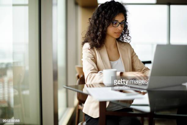 young businesswoman working on laptop at a cafe - online class stock pictures, royalty-free photos & images