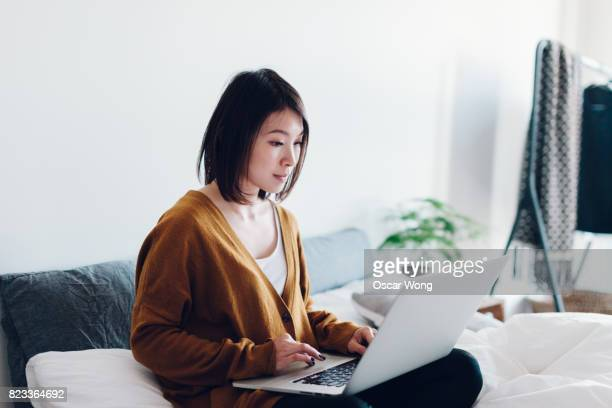 Young businesswoman working on laptop in bedroom