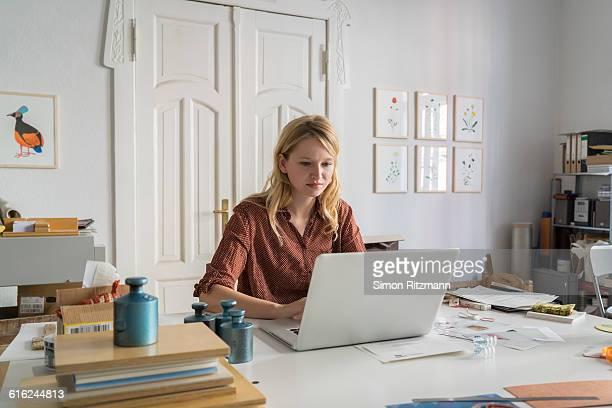 young businesswoman working on laptop - weibliche angestellte stock-fotos und bilder