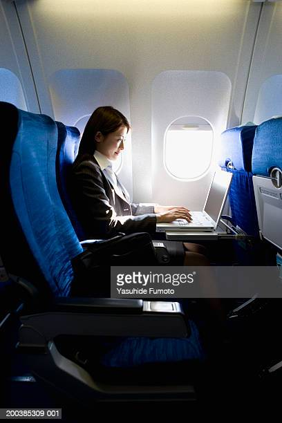 Young businesswoman working on laptop, sitting in airplane, side view
