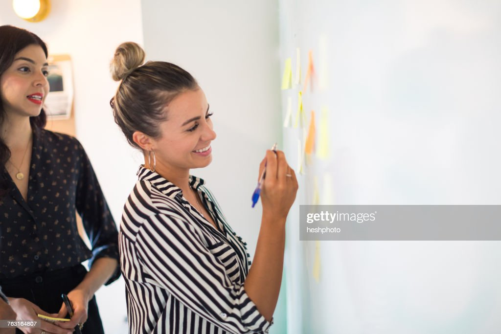 Young businesswoman writing on whiteboard adhesive notes : Stock Photo