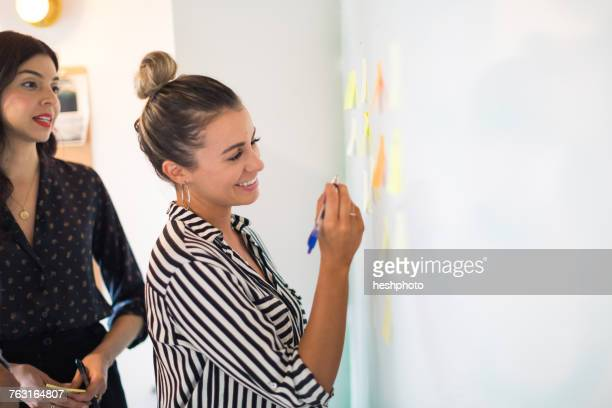 young businesswoman writing on whiteboard adhesive notes - heshphoto stock pictures, royalty-free photos & images