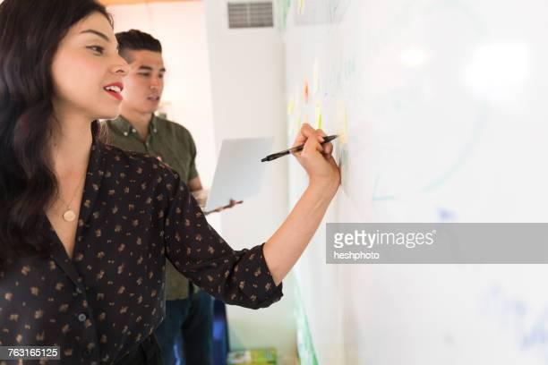 young businesswoman writing on whiteboard adhesive notes - heshphoto stock-fotos und bilder