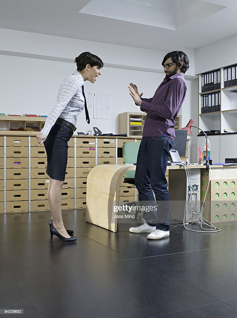 young businesswoman yelling at man in office : Stock Photo