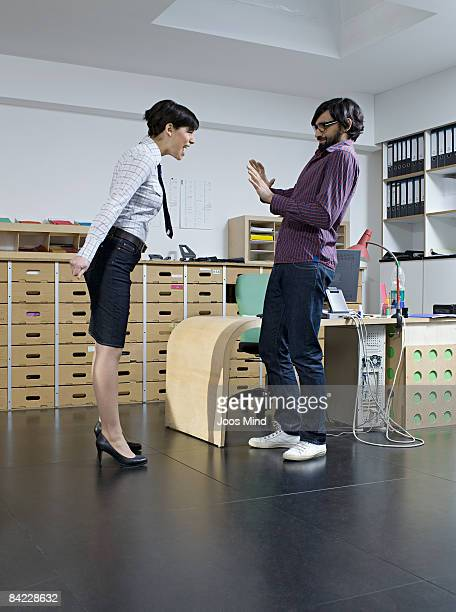young businesswoman yelling at man in office