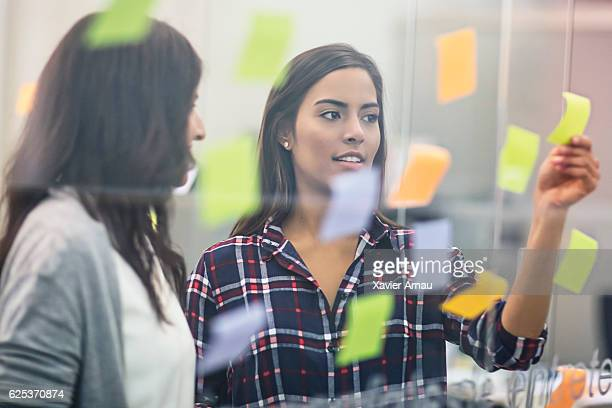 Young businesswomen discussing over sticky notes on glass
