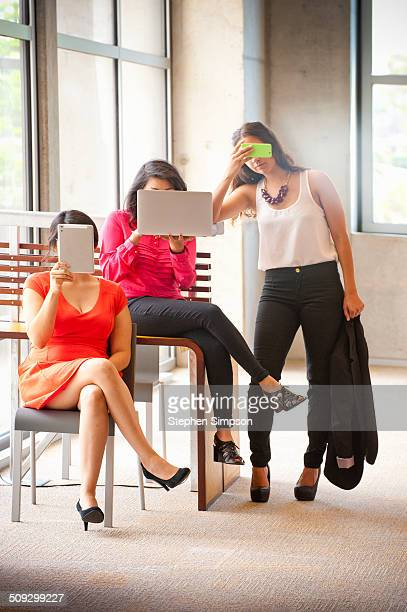 young businesswomen hiding behind their devices