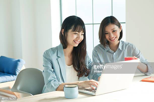 Young businesswomen looking at laptop