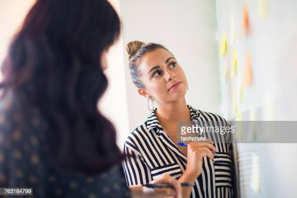 young businesswomen looking at whiteboard adhesive notes - heshphoto - fotografias e filmes do acervo