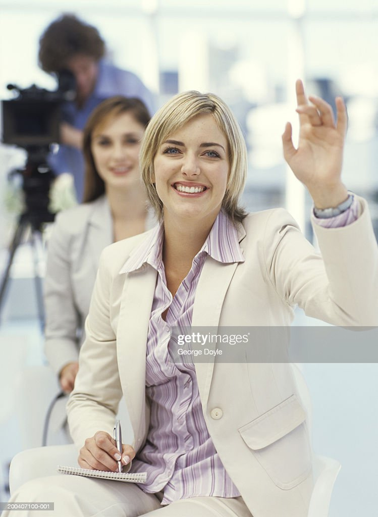 Young businesswomen making notes with hand up, smiling : Stock Photo