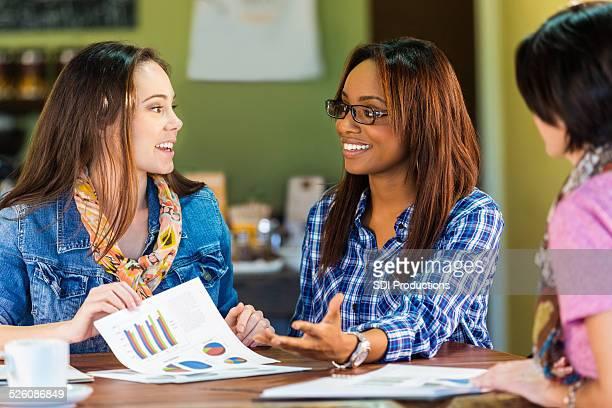 Jóvenes mujeres de negocio reveiwing documentos financieros para pequeños negocios