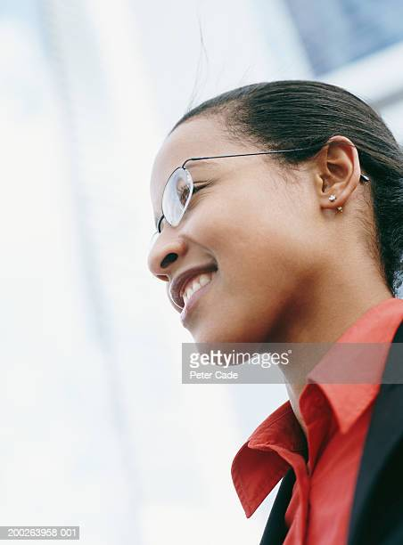 Young busineswoman smiling, side view, close-up