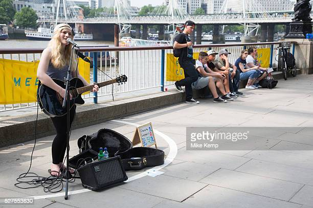 Young busker performing her music both singing and playing guitar on the South Bank The South Bank is a significant arts and entertainment district...