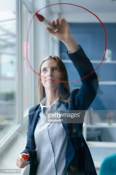 young busnesswoman drawing a pie cahart on a glass screen - drawn circle stock pictures, royalty-free photos & images