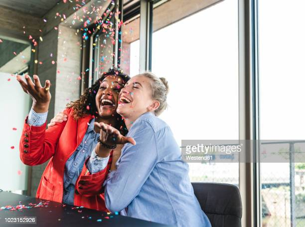 young busniesswomen celebrating success, throwing confetti - feiern stock-fotos und bilder
