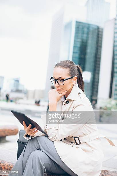 Young bussineswoman sitting and reading e-book