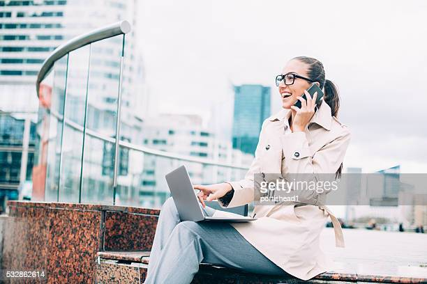 Young bussineswoman using laptop and talking on the phone