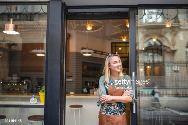 young cafe owner standing with arms crossed at front door - business owner stock pictures, royalty-free photos & images