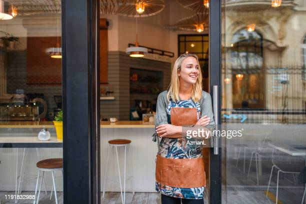 young cafe owner standing with arms crossed at front door - store window stock pictures, royalty-free photos & images
