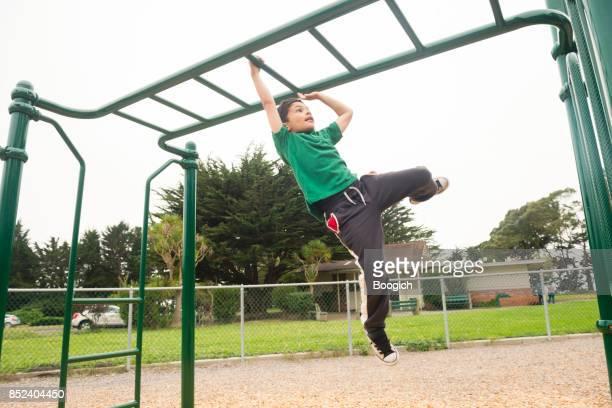 Young California Boy Swinging on Monkey Bars