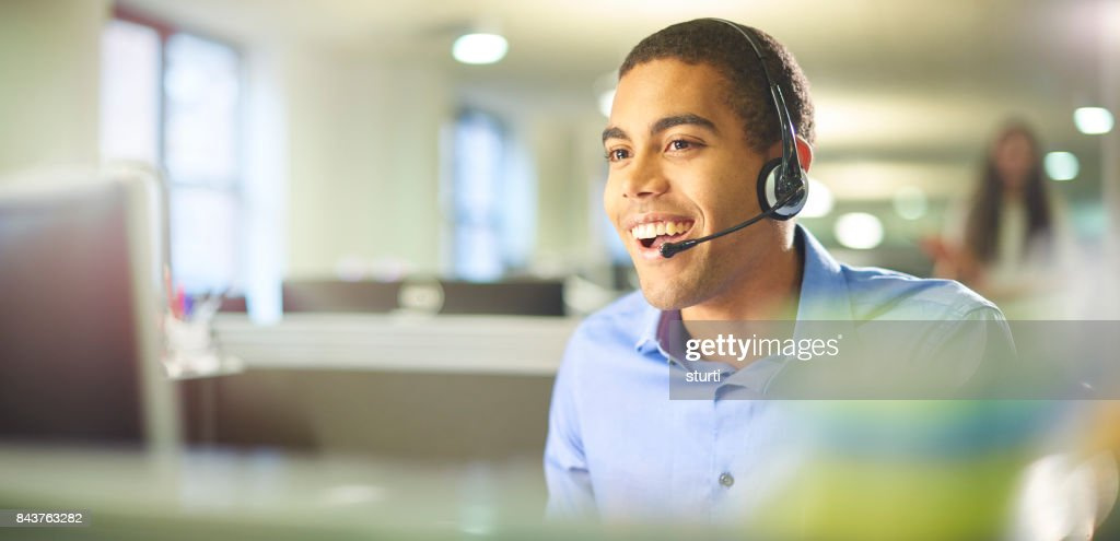 young call centre worker chatting. : Stock Photo