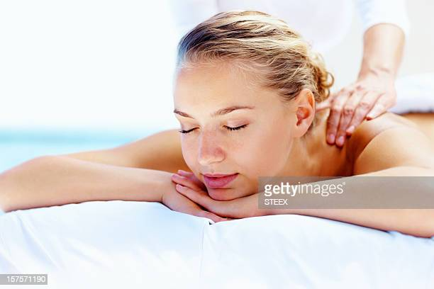 Young calm female receiving a shoulder massage at health spa