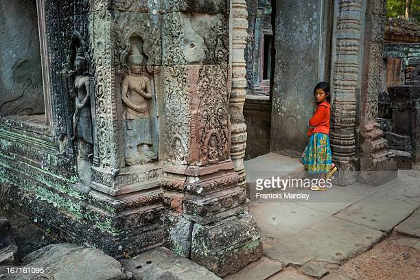 Young cambodian girl leaning against the ruins of the Preah Khan temple in Angkor where stone walls are decorated with statues of Buddhist divinities.