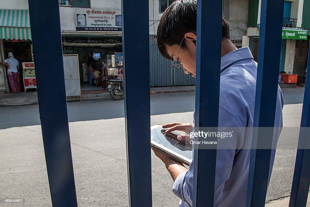 A young Cambodian man uses a tablet to check social media on April 9, 2014 in Phnom Penh, Cambodia. Leaked to the media today, the draft of Cambodia's first-ever cybercrime law, in development since May 2012, is being criticised by international and local human rights organisations for severely restricting freedom of expression online. Article 28 in particular is being criticised for including vague provisions that could be used to silence Cambodian citizens, such as Article 28(3), which prohibits publications 'deemed to generate insecurity, instability and political cohesiveness,' and Article 28(4), which prohibits publications which 'slanders or undermined the integrity of any governmental agencies. Both of these provisions carry with them sentences of one to three years in prison. Internet penetration among the population has drastically increased in recent years and is increasingly serving as an outlet and as a source of information in a country where most media are controlled by the ruling party. Cambodia's government is already under criticism for recent crackdowns on protests and human rights activists, and is accused of frequently using provisions in the Criminal Code and other legislation to unjustly silence civil society and journalists. Human rights activists fear that this new law will exacerbate the situation and provide the government with additional tools to silence its critics online.